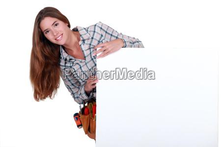 female carpenter holding white sign for