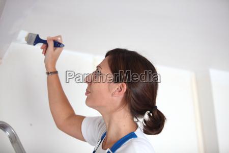 female painter on ladder