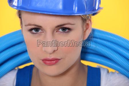 female plumber holding pipes