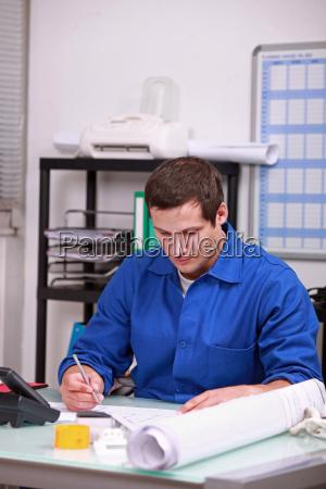 factory worker doing paper work in