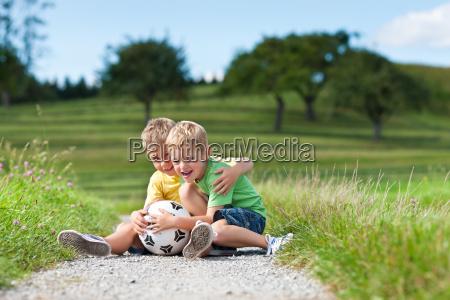 zwei kinder mit fussball sitzen auf
