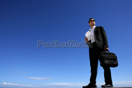 confident businessman in front of blue