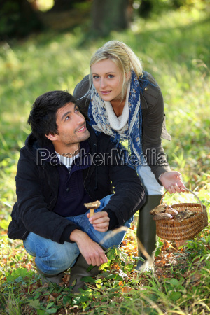 young couple gathering mushrooms in field