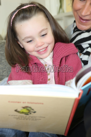 young girl reading a book with