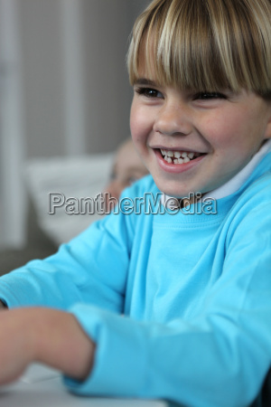 little boy giggling in class