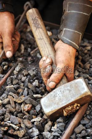detail der schmutzigen haende holding hammer