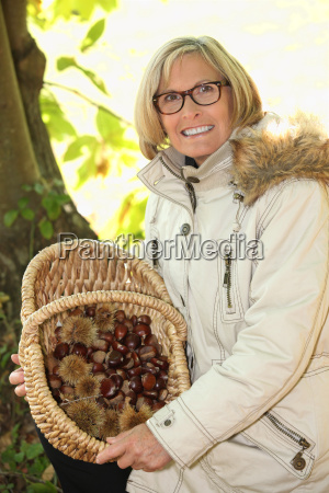 senior woman gathering chestnuts