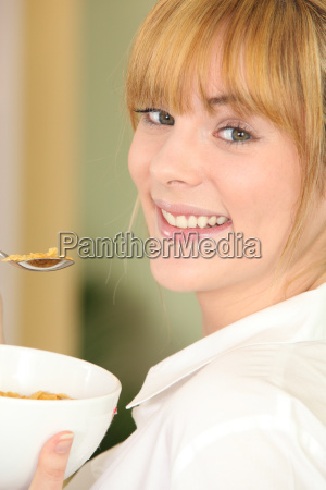 young woman eating a bowl of