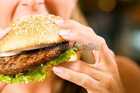 woman at restaurant eating hamburger