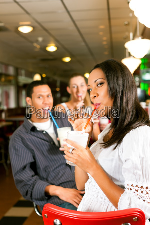 friends drinking milkshakes in a bar