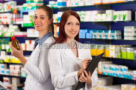 pharmacist with assistant in pharmacy drugstore