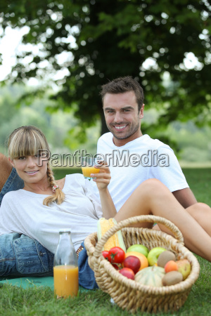 couple with fruit basket in field