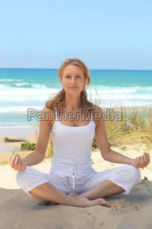 frau die auf dem strand meditiert