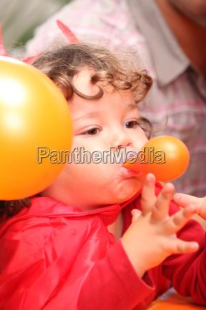 kind sprengt einen ballon
