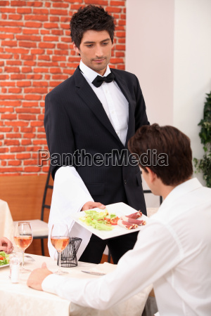 waiter serving a meal in a
