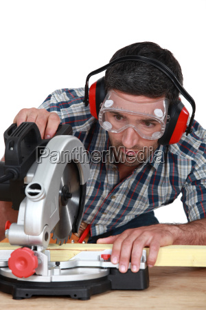 man using circular saw to cut