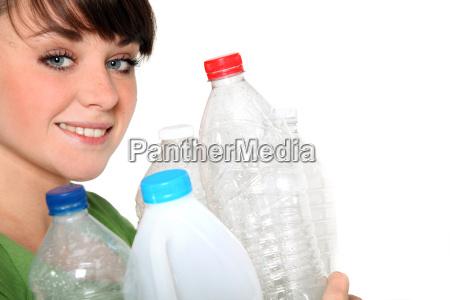 woman holding plastic bottles