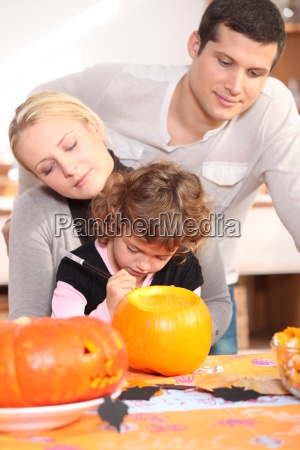 family carving pumpkin