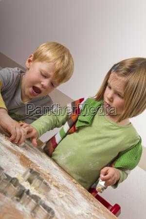 zwei kinder stechen plaetzchen aus