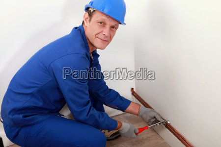 plumber screwing copper water pipes in