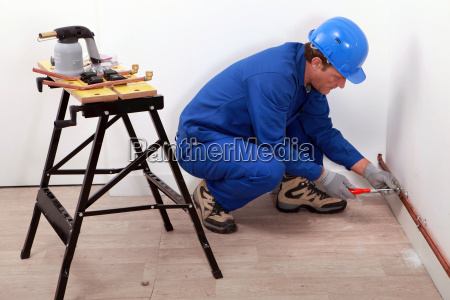 plumber fitting copper pipes to a