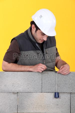 a mason using a plumb bob