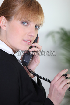redhead using an office telephone