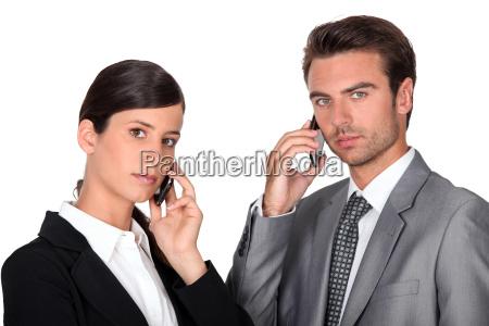 executive couple using cellphones