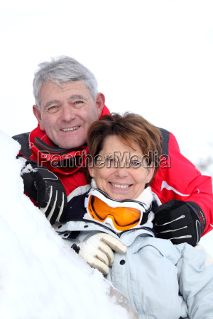 smiling senior couple laid in snow