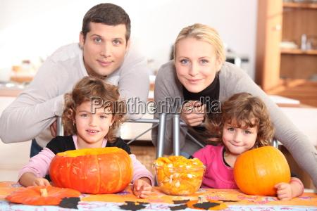 a family carving halloween pumpkins
