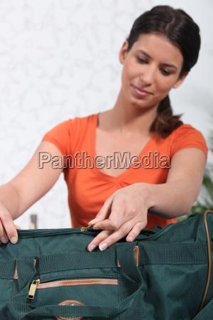 frau die gruene tasche verpackt