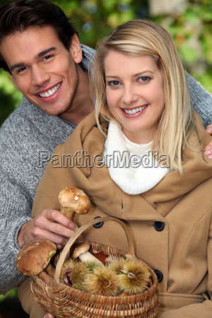 young couple gathering mushrooms and chestnuts