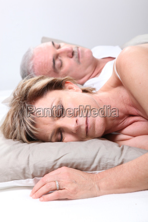mature couple asleep in bed