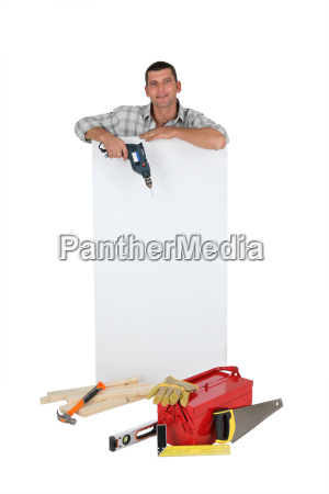 man holding drill next to blank
