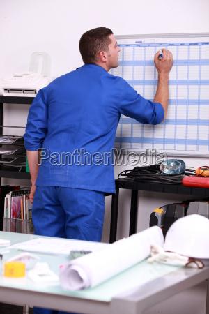 junger techniker schreibt auf einem kalender
