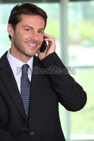 smiling businessman using a telephone