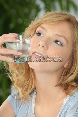 junge blondine mit einem glas wasser