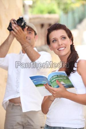 touristen mit kamera und reisefuehrer