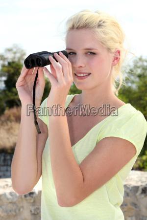 blonde frau beobachtet durch fernglas