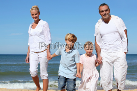 young family walking along a sandy