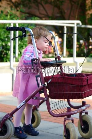 kind spielt mit einem rollator