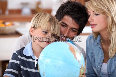 junge familie auf einem globus suchen