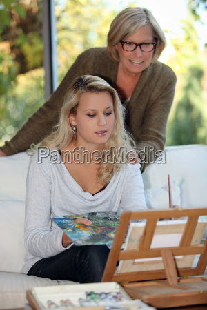 woman painting as mother watches