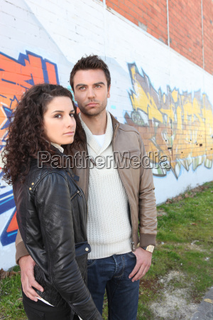 fashionable young couple stood by wall