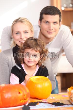 little girl with parents preparing pumpkin