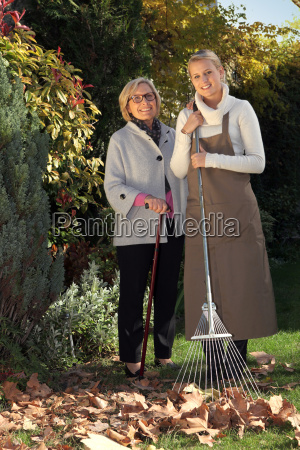 mother and daughter raking leaves