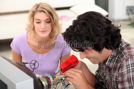 couple repairing television