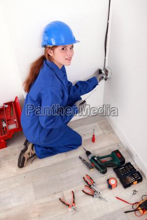 female electrician fixing a wall socket