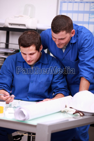 electricians looking at a part