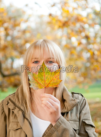 young woman with autumn leaf